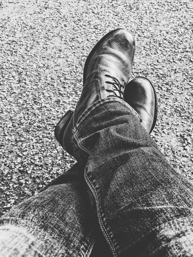 Crossed leg in jeans and leather boots black and white