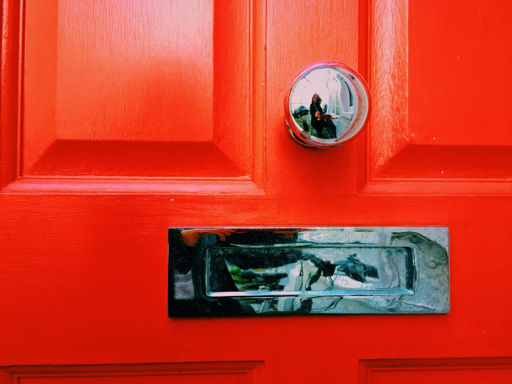 Silver mail box on a red door