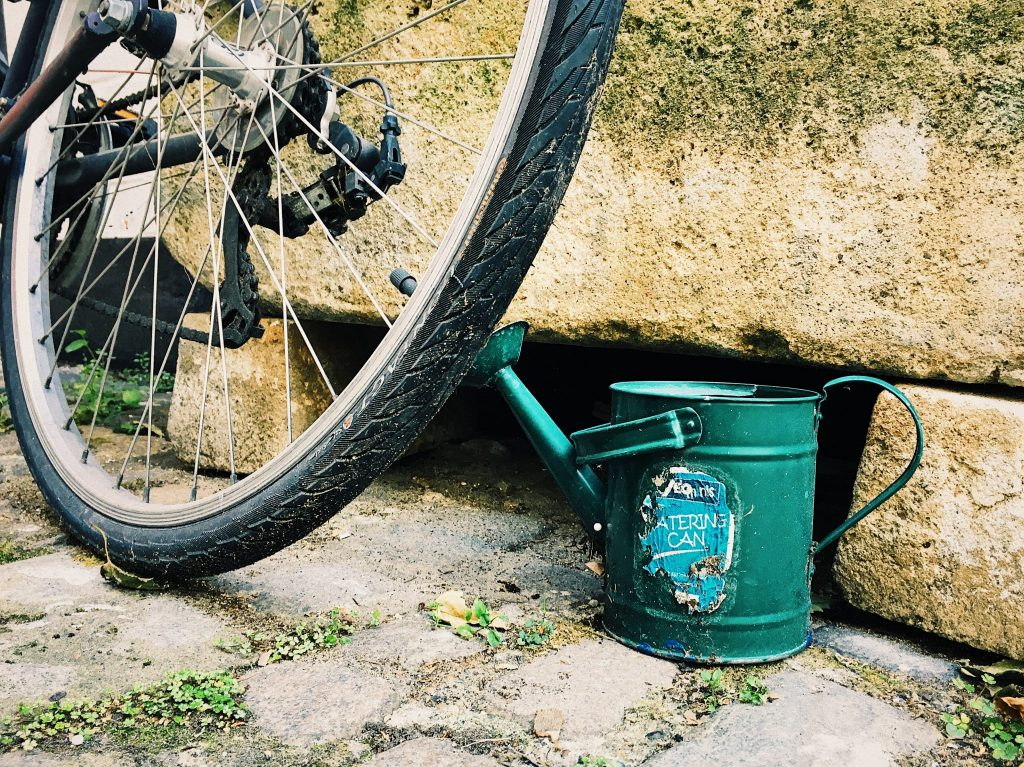 Small green metal watering can standing on the street next to a bicycle