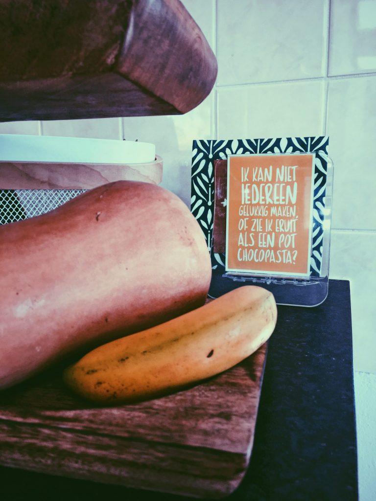 Banana, pumpkin and postcard on kitchen shelf