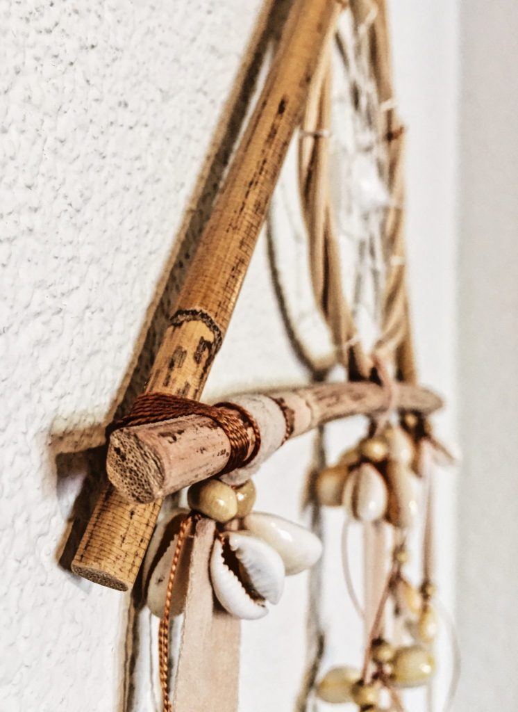close-up of dreamcatcher made of bamboo and sea shells