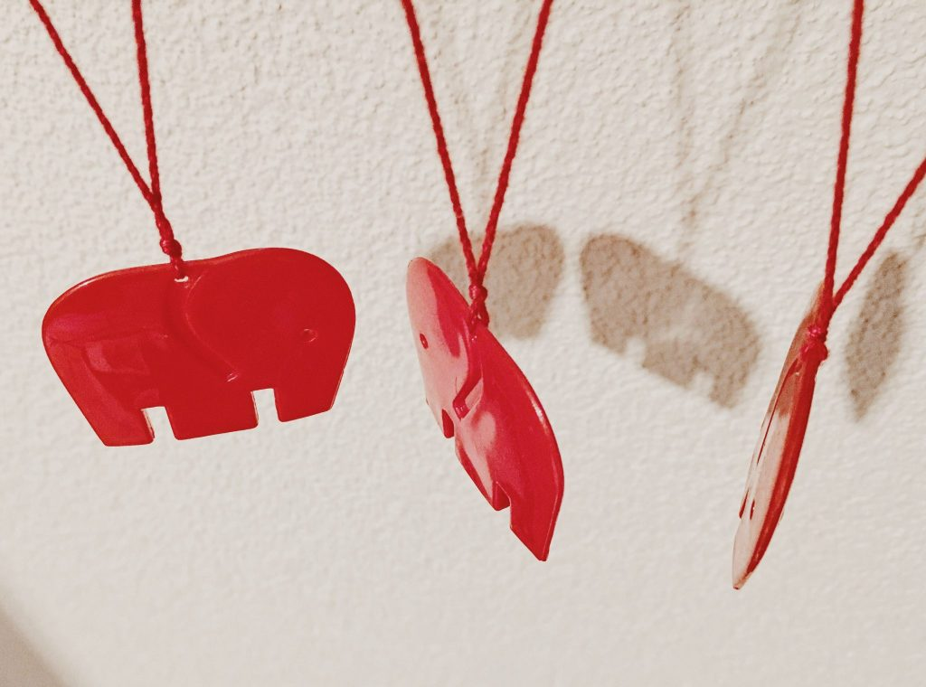 three red plastic elephants hanging from a shelf