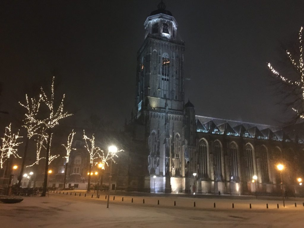 View of church and snow covered streets in Deventer by night